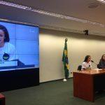 A foto mostra um telão à esquerda com a imagem da deputada Larissa Pinho Maciel, que está na mesa da Comissão defendendo o seu projeto de lei, que determina a inclusão do ensino de inglês desde o ensino fundamental