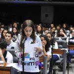 A foto mostra o plenário da Câmara dos Deputados cheio de alunos e a aluna Cristina Azevedo, do quinto ano do Colégio Marista, está defendendo um projeto de lei ao microfone posicionada na ponta de uma das bancadas onde os deputados ficam sentados durante as sessões.