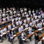 A foto mostra os deputados mirins de todo o Brasil em pé ouvindo o Hino Nacional antes do início da sessão do Câmara Mirim 2016. Estão todos posicionados à frente de suas cadeiras no Plenário Ulysses Guimarães.