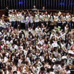 A foto mostra o aglomerado de deputados mirins, muito alegres e eufóricos, embaixo da mesa diretora do Plenário Ulysses Guimarães, comemorando o encerramento, com sucesso, do Câmara Mirim 2016. Estão todos sorridentes com as mãos para o alto em sinal de celebração.