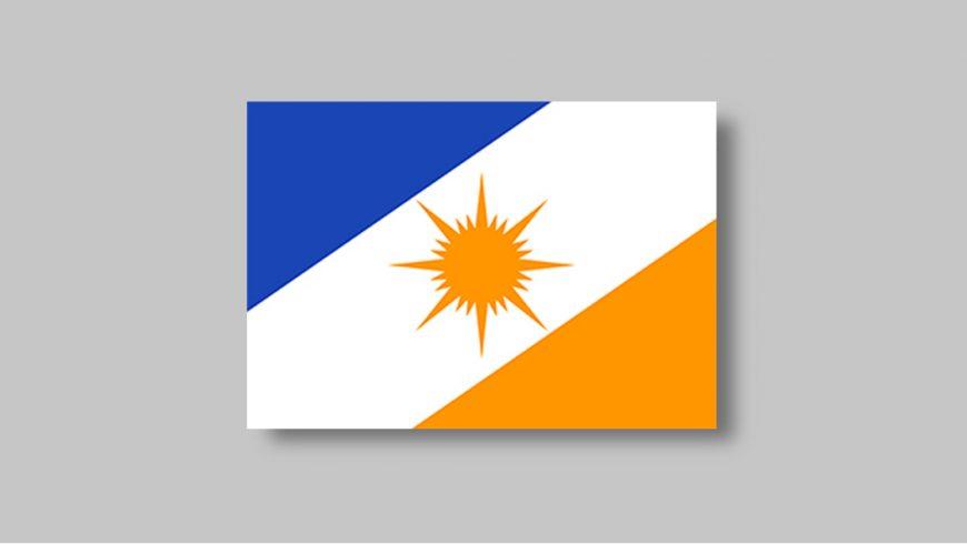 Retângulo dividido em três partes. Na diagonal, uma faixa branca e larga atravessa a bandeira da ponta inferior esquerda até a extremidade superior direita. No centro da bandeira, a figura estilizada de um sol amarelo. As partes da bandeira que ficam de fora da faixa formam dois triângulos: o superior é azul e o inferior, amarelo.