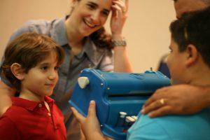 Alejandro entrega a máquina de escrever em braile a um menino que não pode enxergar, na Laramara