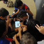 A fotografia tirada de cima mostra seis crianças sentadas sobre um tapete bege. Um menino segura um tablet e navega pelo portal do Plenarinho enquanto as outras crianças observam interessadas.