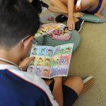 Fotografia mostra um menino de costas sentado sobre tapete bege. Ele lê uma revistinha em quadrinhos do plenarinho. Na frente do menino estão algumas almofadas e, sobre elas, outras revistinhas em quadrinhos. No topo da imagem, mais duas crianças sentadas aparecem parcialmente.