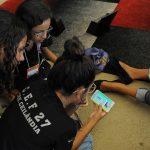Fotografia. Sobre um tapete colorido, três crianças estão sentadas. Uma delas segura um celular que mostra na tela o Super Jogo da saúde do Plenarinho. As outras duas crianças observam o celular atentos.