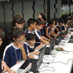 Fotografia. Várias crianças com uniforme de escola azul-escuro com detalhes brancos usam computadores portáteis que estão sobre uma comprida mesa branca em um salão com piso preto e paredes de mármore branco;