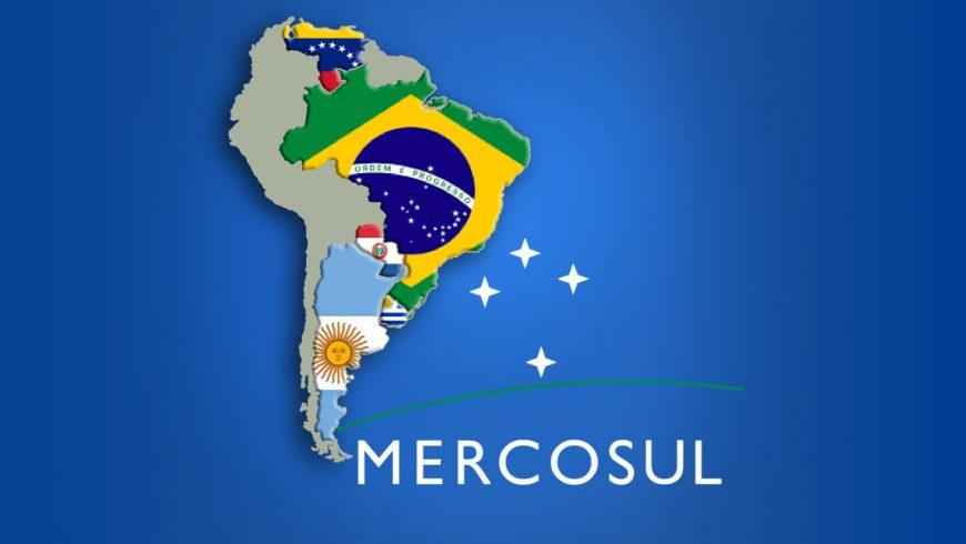 Ilustração. Imagem com fundo azul. Ao centro, imagem da América do Sul. Destacados, com a imagem de suas bandeiras dentro dos seus limites territoriais, estão os países que compõem o Mercosul: Brasil, Argentina, Uruguai, Paraguai e Venezuela.