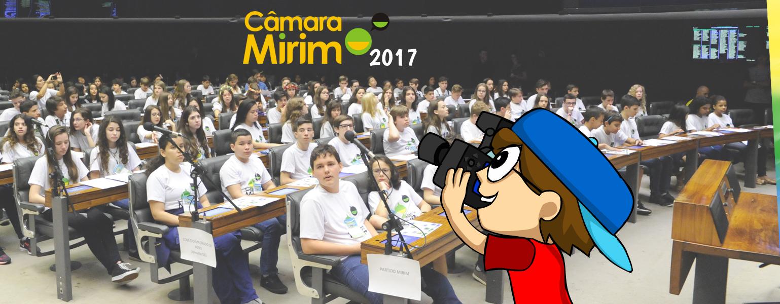 """Fotografia que mostra o Plenário Da Câmara dos Deputados cheio de crianças sentadas nas bancadas. As crianças usam camiseta branca. Do lado direito, deseenho do Adão com uma câmera fotográfica na mão, como se fotografasse as crianças. No topo da imagem, ao centro, as palavras """"Câmara Mirrim"""" escritas em amarelo e """"2017"""" em branco."""