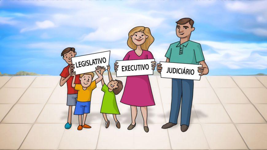 Ilustração. Ao fundo, vê-se o céu azul com nuvens brancas. O piso é de quadrados brancos. Ao centro, uma família segura cartazes com as algumas palavras. Os filhos, dois meninos e uma menina, seguram a placa com a palavra legislativo. A mãe, com executivo. E o pai, com Judiciário. O pai veste uma calça azul e uma camiseta polo verde. Tem cabelos curtos e castanhos. A mãe está de vestido rosa, é loira e sorri. Ao seu lado, a filha menor usa um vestido verde e tem cabelos castanhos curtos com franja. O irmão que está ao seu lado, usa short azul, camiseta polo laranja e sapatos vermelhos. É um pouco maior do que a menina. O irmão maior está de short cinza, camisa polo vermelha e sapatos azuis.